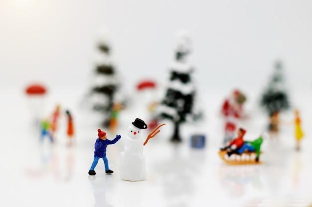 Gens miniatures: les enfants s'amusent avec bonhomme de neige. Photo Premium