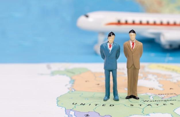 Gens miniatures, homme d'affaires debout sur la carte américaine Photo Premium
