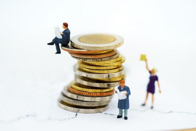 Gens miniatures: livre de lecture de l'équipe des affaires sur la pile de pièces Photo Premium