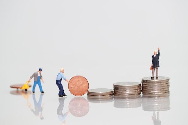 Gens miniatures: travailleur avec pièce de monnaie et homme d'affaires, concept d'entreprise utilisant comme arrière-plan Photo Premium