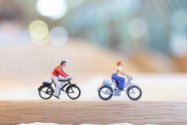 Gens miniatures à vélo sur un pont en bois Photo Premium