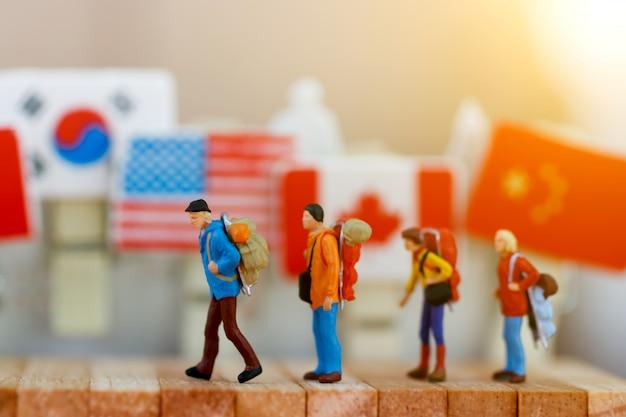 Gens Miniatures: Voyageur Avec Sac à Dos Marchant Dans Une Boîte En Bois. Photo Premium