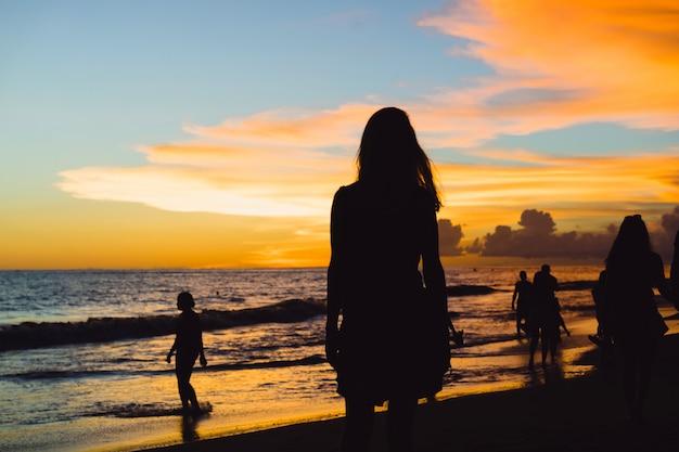 Les gens sur la plage au coucher du soleil. Photo gratuit