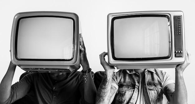 Des gens qui tiennent une télévision rétro l'un à côté de l'autre Photo gratuit