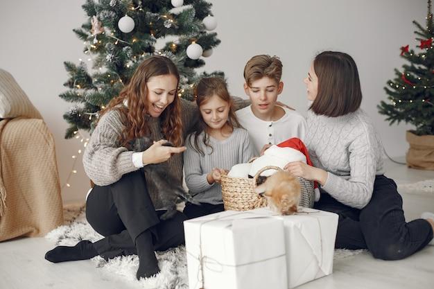 Les Gens Réparent Pour Noël. Des Gens Assis Près De L'arbre De Noël. Photo gratuit