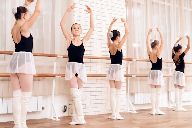 Les gens se tiennent dans différentes positions près de la barre de ballet. Photo Premium