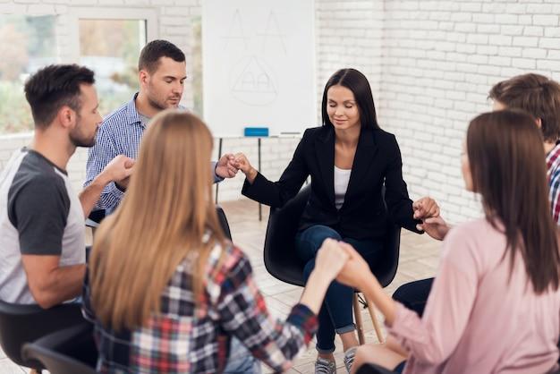 Les gens sont assis et se tiennent la main lors d'une séance de thérapie. Photo Premium