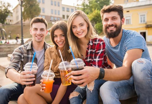 Les gens sourient et boivent du jus dans la rue ensemble. Photo Premium