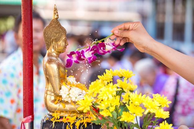 Des gens versent de l'eau à une statue bouddhiste et bénissent en thaïlande le festival annuel de songkran dans un temple bouddhiste Photo Premium
