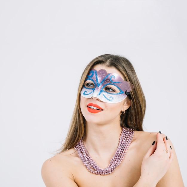 Gentil jeune femme souriante en masque de carnaval mascarade portant collier Photo gratuit
