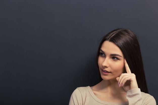 Gentil jeune fille regarde au loin et réfléchit. Photo Premium