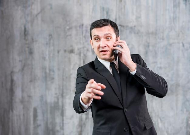 Gentil jeune homme d'affaires élégant parlant au téléphone Photo gratuit