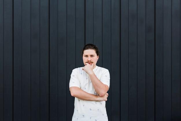 Gentil jeune homme avec sa main sur le menton debout contre un mur rayé noir Photo gratuit