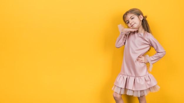 Gentil petite fille posant sur fond jaune Photo gratuit