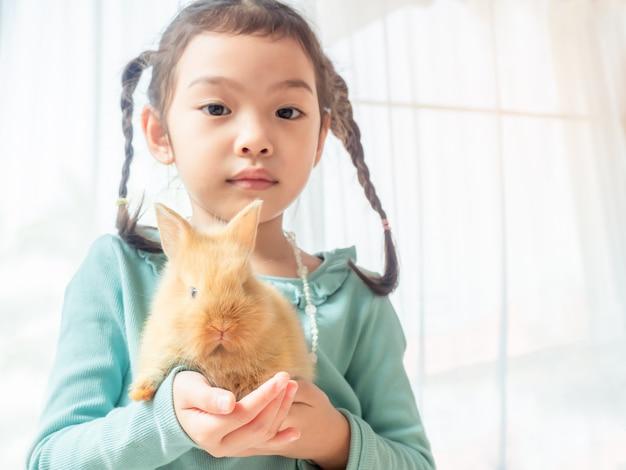Gentille petite fille mignonne tenant un bébé lapin brun dans les mains. Photo Premium