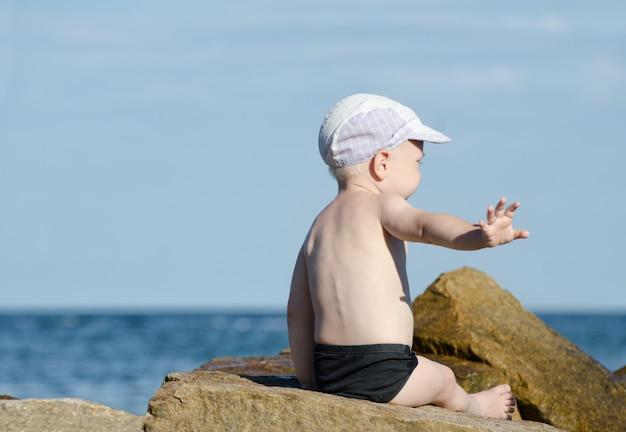 Le geste de ne pas déranger. petit garçon en maillot de bain est assis au bord de la mer, place pour le texte Photo Premium