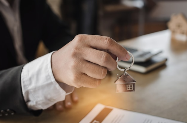 Gestionnaire de courtier immobilier donnant la clé de la maison au client après la signature du contrat Photo Premium