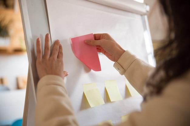 Gestionnaire Femelle Coller Des Notes De Papier Vierge Sur Le Tableau De Conférence Photo gratuit