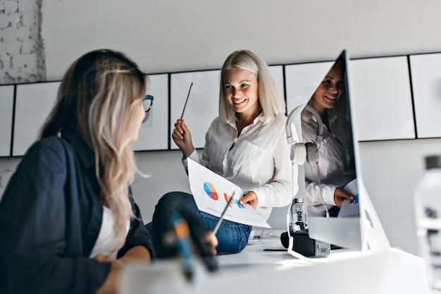 Gestionnaire De Femme Blonde Souriante Tenant Infographie Et Crayon, Assis Sur La Table. Portrait Intérieur De Deux Femmes Travaillant Avec Ordinateur Au Bureau. Photo gratuit