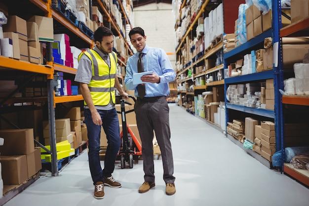 Gestionnaire montrant une tablette à un ouvrier dans un entrepôt Photo Premium