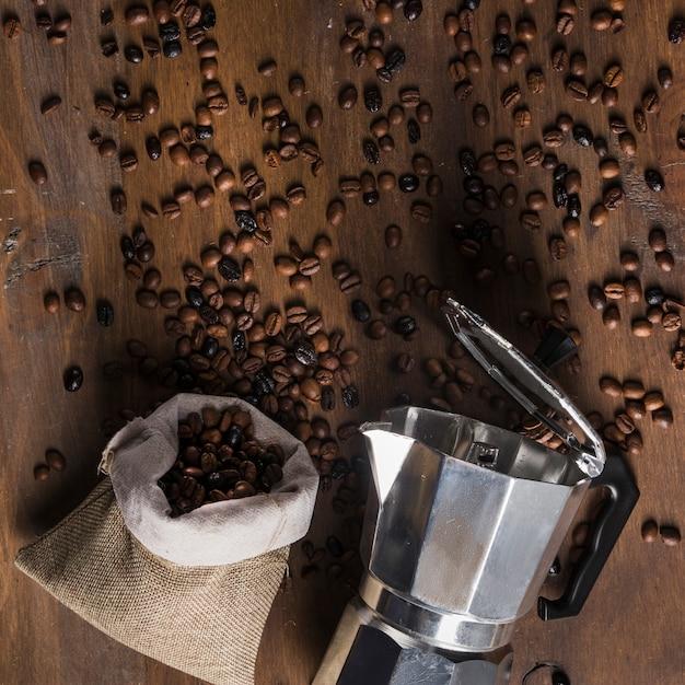 Geyser cafetière et sac avec grains dispersés Photo gratuit