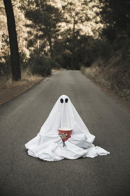 Ghost avec boîte de pop-corn assis sur une route de campagne Photo gratuit