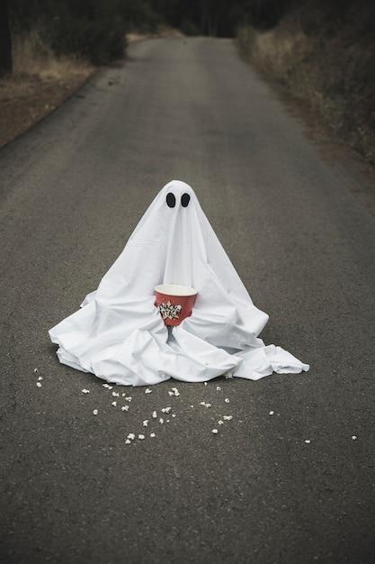 Ghost avec boîte de pop-corn assis sur la route avec des grains étalés Photo gratuit