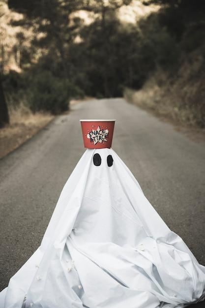 Ghost avec boîte de pop-corn sur la tête assis sur une route de campagne Photo gratuit