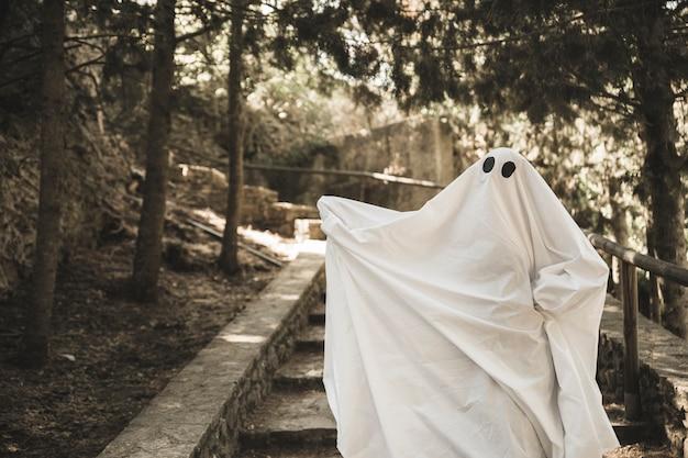 Ghost avec les mains sur les marches dans le parc Photo gratuit