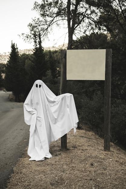 Ghost pointant sur un panneau Photo gratuit
