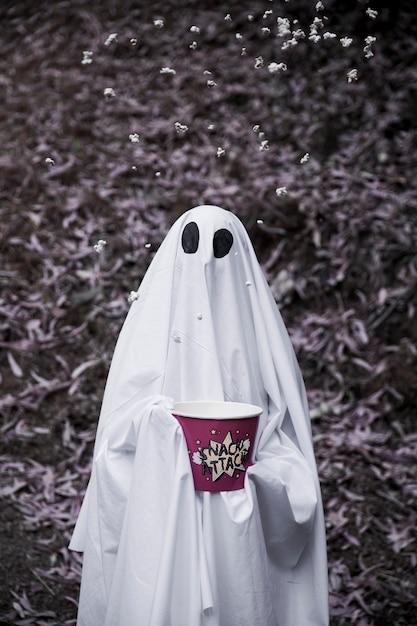 Ghost tenant une boîte de pop-corn avec du pop-corn dans l'air Photo gratuit