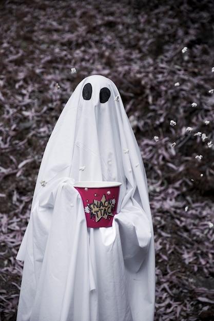 Ghost tenant une boîte de pop-corn avec des grains qui tombent Photo gratuit