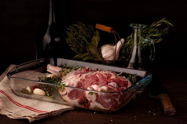 Gigot d'agneau cru prêt à rôtir avec ail et fines herbes Photo Premium