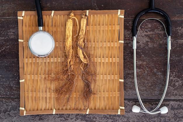 Ginseng sec sur armure de bambou avec stéthoscope sur le fond de bois Photo Premium