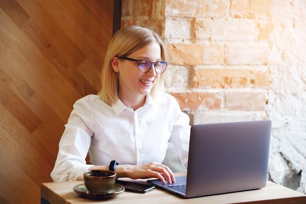 Girl manager, pigiste, femme d'affaires travaillant sur un ordinateur portable dans un café ou co-travaillant. Photo Premium