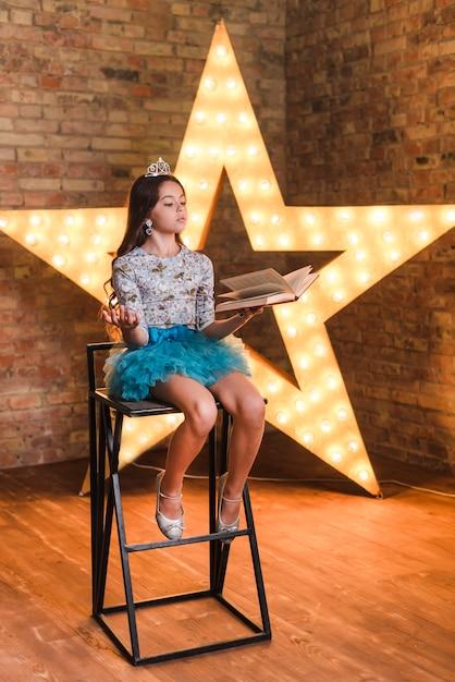 Girl, séance, sur, chaise haute, répéter, devant, brillant, étoile, contre, mur brique Photo gratuit