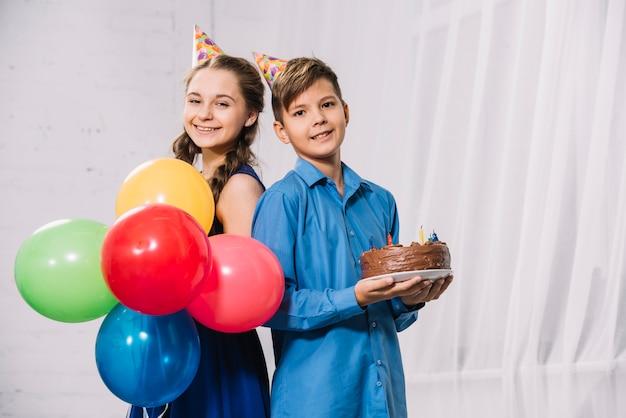 Girl, tenue, ballons, et, garçon, tenue, gâteau anniversaire, dos dos, regarder appareil-photo Photo gratuit