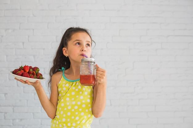 Girl, tenue, plaque, de, fraises rouges, boire, fraises, smoothies Photo gratuit