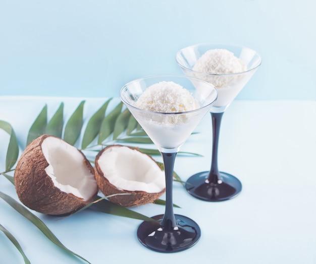 Glace à la noix de coco sur le fond bleu avec feuille de palmier et noix de coco Photo Premium