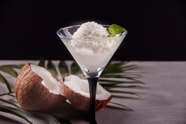 Glace à la noix de coco sur la table grise avec feuille de palmier et noix de coco Photo Premium