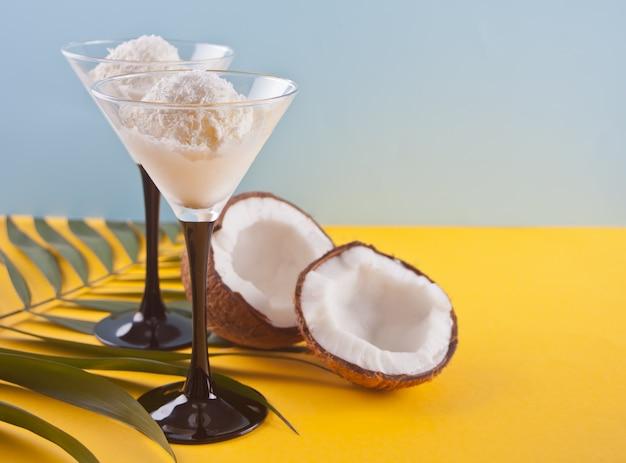 Glace à la noix de coco sur la table jaune avec feuille de palmier et noix de coco Photo Premium
