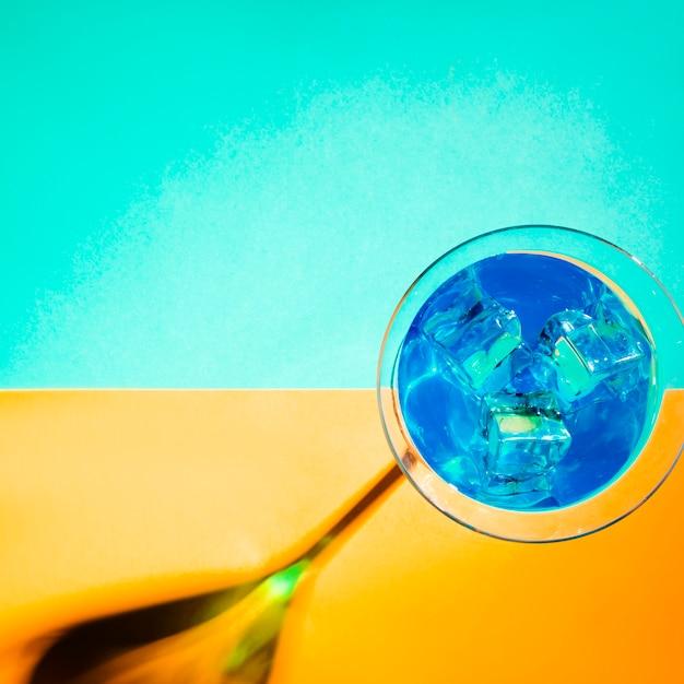 Glaçons dans le verre à martini bleu sur fond jaune et turquoise Photo gratuit