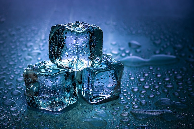 Les glaçons et l'eau fondent sur un fond froid Photo Premium