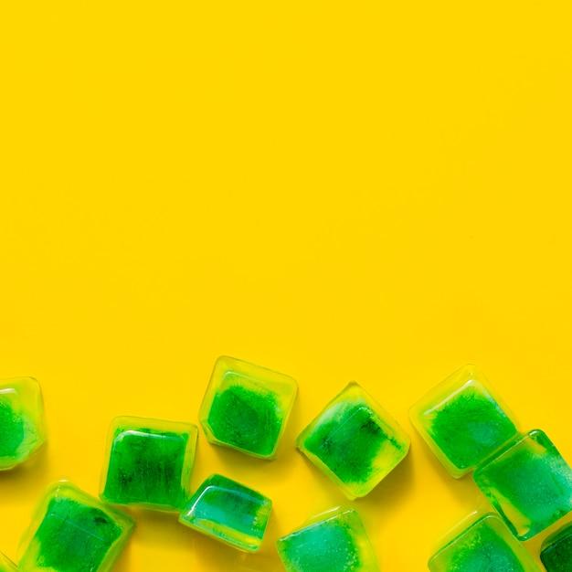 Glaçons verts sur fond jaune Photo gratuit
