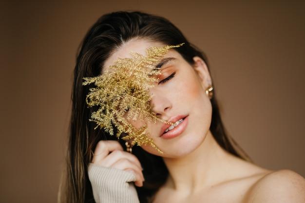 Glamour Jeune Femme Posant Les Yeux Fermés Sur Un Mur Marron. Dame Agréable De Bonne Humeur Tenant Une Plante. Photo gratuit