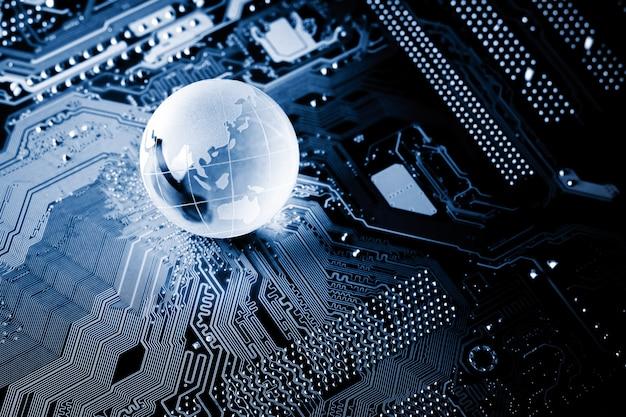 Globe de cristal bleu étincelant sur une carte de circuit informatique dans le noir. Photo Premium