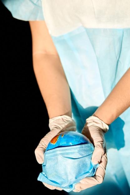 Globe Dans Un Masque Médical Entre Les Mains Du Médecin à La Lumière Dure Photo Premium