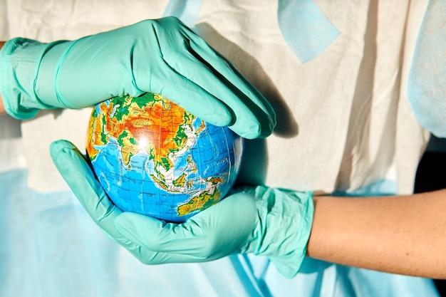 Globe Entre Les Mains Du Médecin Sous Une Lumière Dure Photo Premium