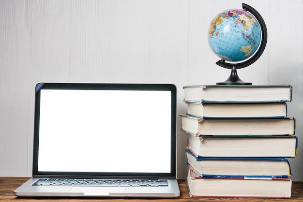 Globe et livres près d'ordinateur portable Photo gratuit