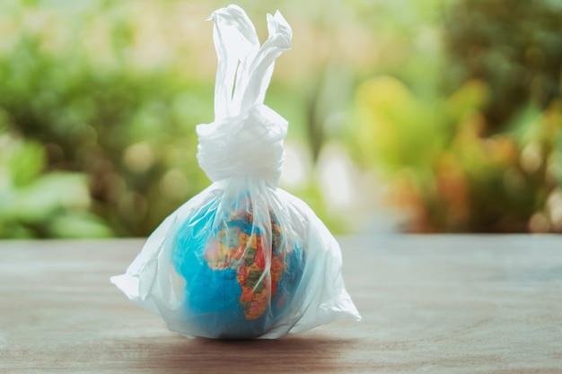 Globe terrestre concept jour dans un sac en plastique sur la table Photo Premium